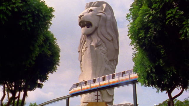 vídeos y material grabado en eventos de stock de wide shot monorail train passing in front of giant 'merlion' statue / singapore - monorraíl