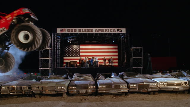 wide shot monster trucks flying through the air and rolling over row of cars as country band plays on stage - arts culture and entertainment stock videos & royalty-free footage