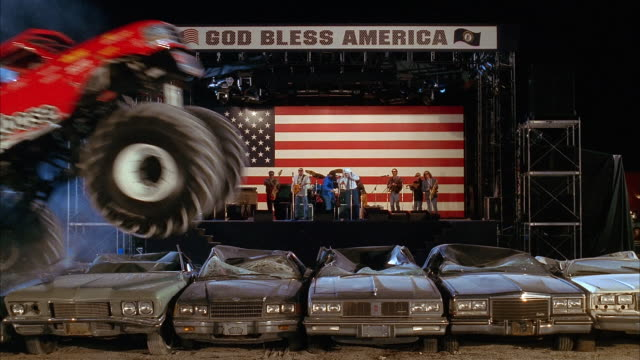 wide shot monster trucks flying through the air and rolling over row of cars as country band plays on stage - 1998 stock-videos und b-roll-filmmaterial