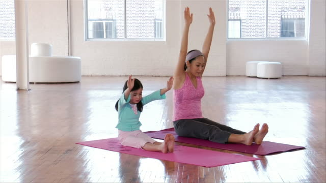 wide shot mother and daughter doing yoga/ brooklyn, new york - bambine femmine video stock e b–roll