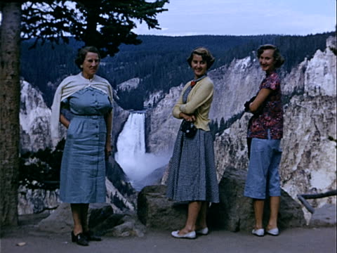 vídeos de stock, filmes e b-roll de 1951 wide shot mother and two teenage daughters standing at viewpoint overlooking waterfall and rocky mountains in british columbia glacier national park / montana , usa  - glacier national park us