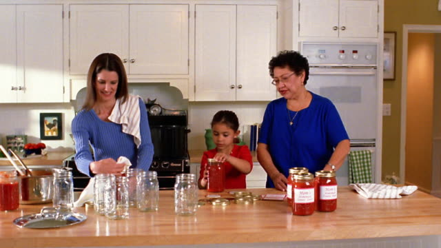 stockvideo's en b-roll-footage met wide shot mother, grandmother and daughter sealing tomato sauce into canning jars in kitchen - glazen pot