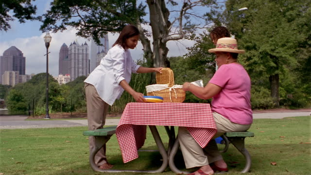 vidéos et rushes de wide shot mother, grandmother and daughter setting up picnic on picnic table in piedmont park / atlanta - panier de pique nique