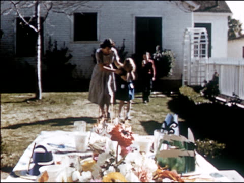 vidéos et rushes de 1954 wide shot mother leading young girl covering her eyes into backyard / stopping in front of party table / girl opening eyes / audio - 1954