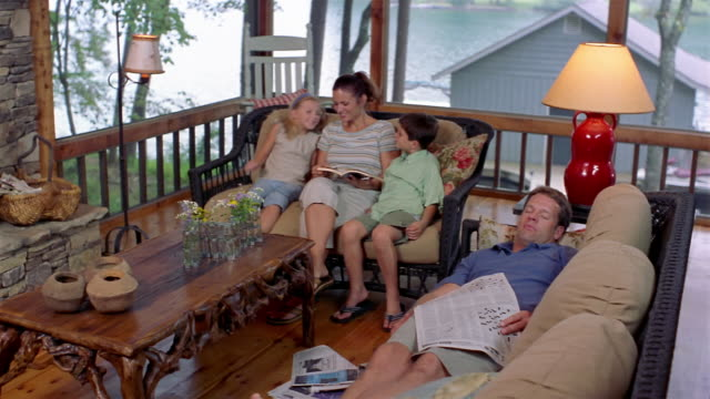 wide shot mother reading book to children and father napping on couch in lakehouse with view of lake in background - clarkesville stock videos & royalty-free footage