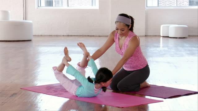 wide shot mother teaching yoga to daughter/ brooklyn, new york - 弓のポーズ点の映像素材/bロール