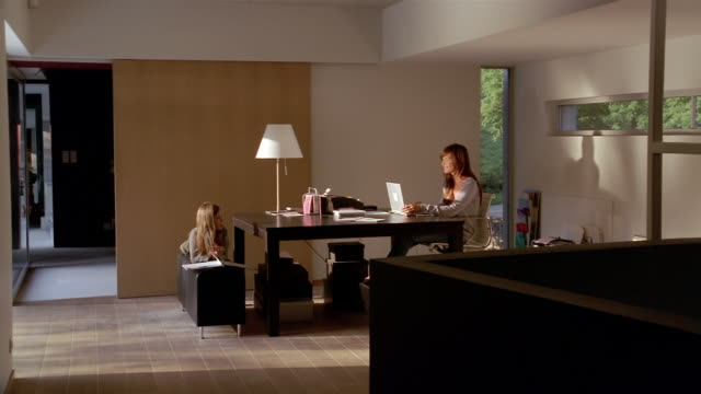 wide shot mother working on laptop and daughter reading book at table in home office - wide shot stock videos & royalty-free footage