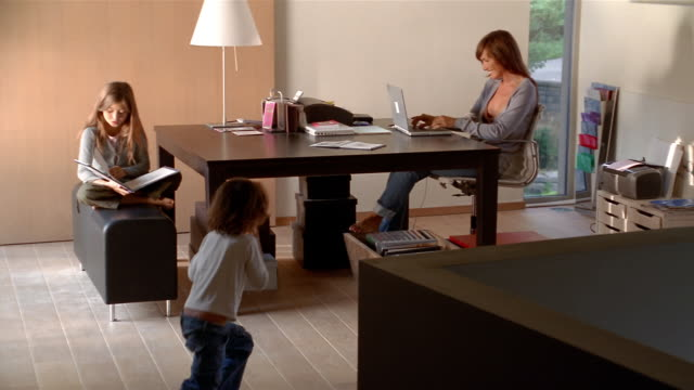 wide shot mother working on laptop, daughter reading book and son playing with toy on floor in home office - fax machine stock videos & royalty-free footage