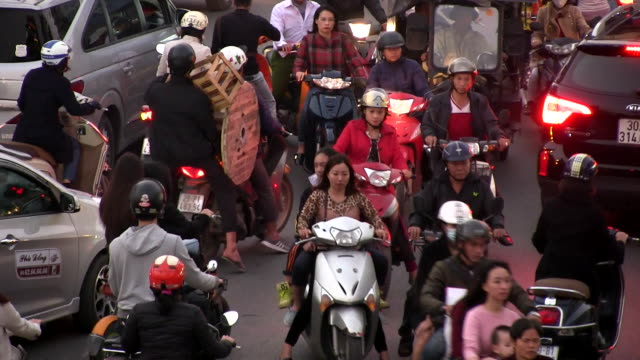 wide shot - motorcycles, bikes, buses weave a net in hang gai street of hanoi. - 人力車点の映像素材/bロール
