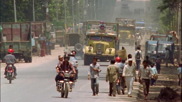 vidéos et rushes de wide shot motorcycles, trucks and pedestrians on street / nepal - véhicule utilitaire léger