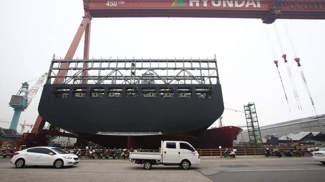 wide shot motorcycles trucks vans and cars pass in front of a ship under construction in a dry dock as a crane moves overhead medium shot motorcycles... - skeppsbyggare bildbanksvideor och videomaterial från bakom kulisserna