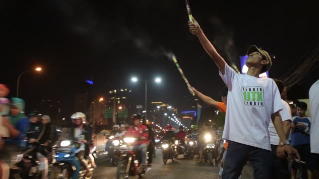 Wide shot motorists drive past during Takbiran celebrations on the night before Eid alFitr in Jakarta Indonesia Medium shot low angle a boy releases...