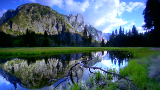 Wide shot mountain and trees reflecting in lake with clouds in sky / Yosemite National Park, California