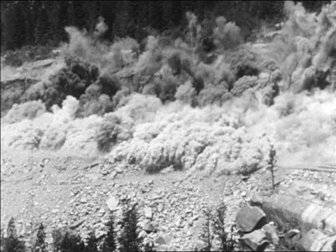 b/w 1929  wide shot mountainside exploding in clouds of dust - explosive stock videos & royalty-free footage