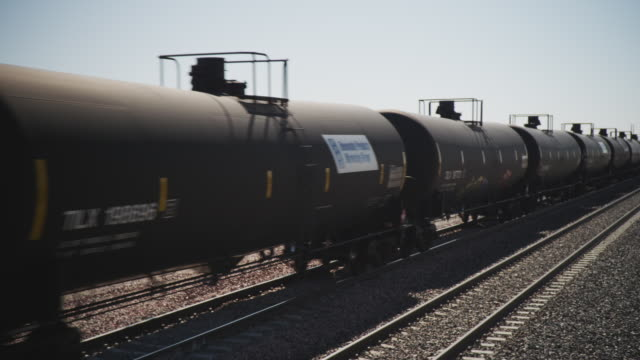 wide shot multiple black, oil, train cars pass camera. - silo stock videos & royalty-free footage