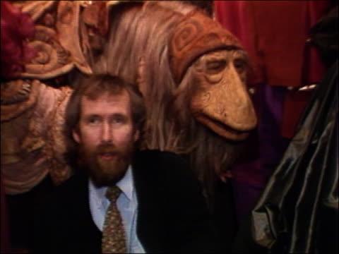 vídeos de stock e filmes b-roll de 1982 wide shot muppet creator jim henson smiling with'dark crystal' character model and four women - 40 49 anos