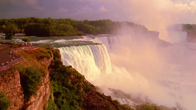 wide shot niagara falls with mist surrounded by trees on sunny day / ontario, canada - niagara falls stock videos and b-roll footage