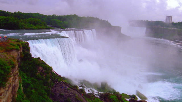 Wide shot Niagara Falls with mist surrounded by trees / Ontario, Canada