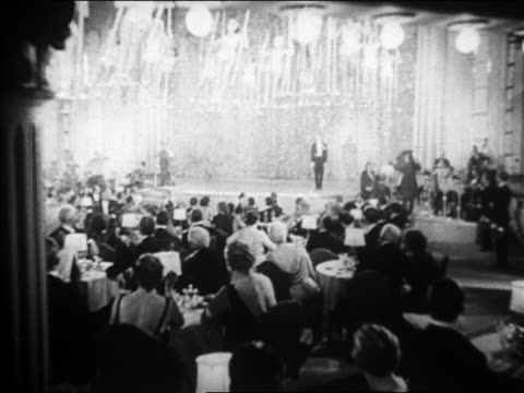 vídeos de stock e filmes b-roll de b/w 1928 wide shot nightclub with women on swings above head of audience / nyc / newsreel - elegante