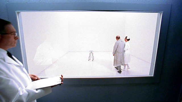 Wide shot nurse bringing mental patient into white room / medium shot doctors observing through window in foreground