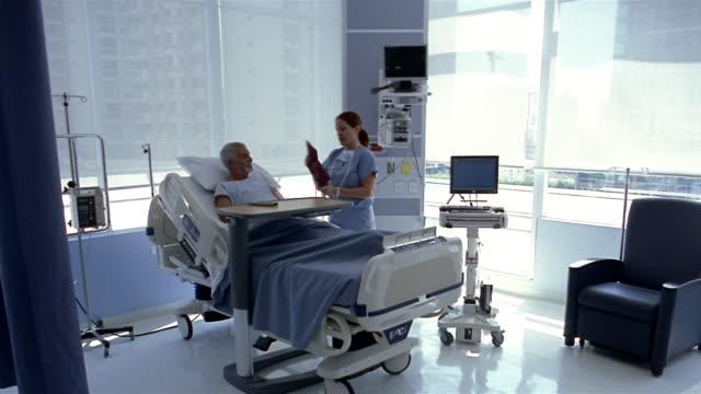 Wide shot Nurse taking mature patient's blood pressure in hospital room/ Panama City, Panama