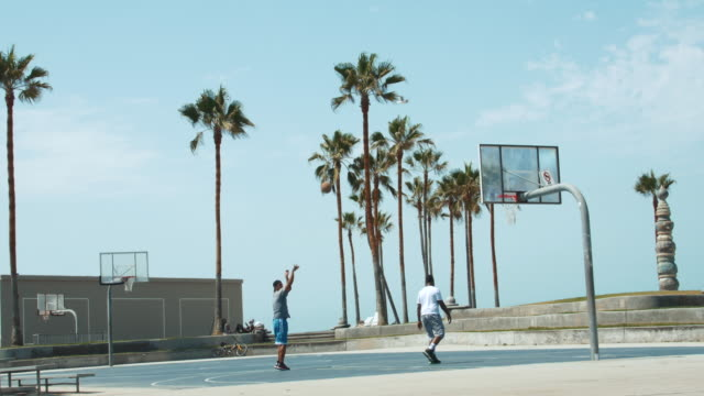 wide shot of 2 men shooting hoops on an exterior basketball court at venice beach in los angeles - wide stock videos & royalty-free footage