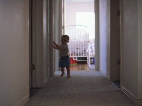 wide shot of a baby boy carefully working his way down a hallway as he is just barely learning to walk - solo un bambino maschio video stock e b–roll