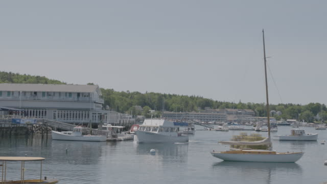 Wide shot of a boat arriving in Boothbay Harbor