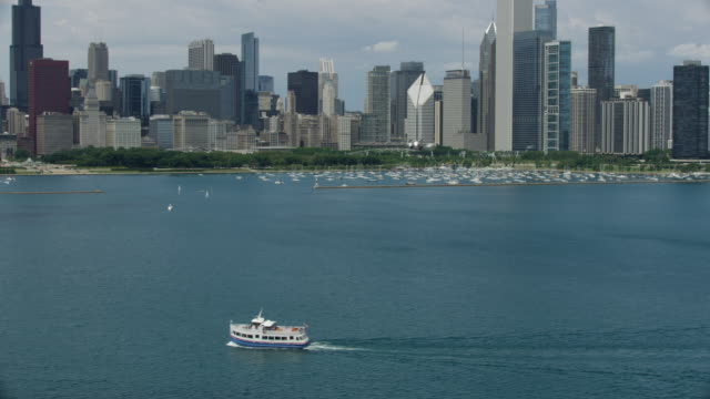 wide shot of a boat on the lake michigan with downtown chicago in the background - lago michigan video stock e b–roll