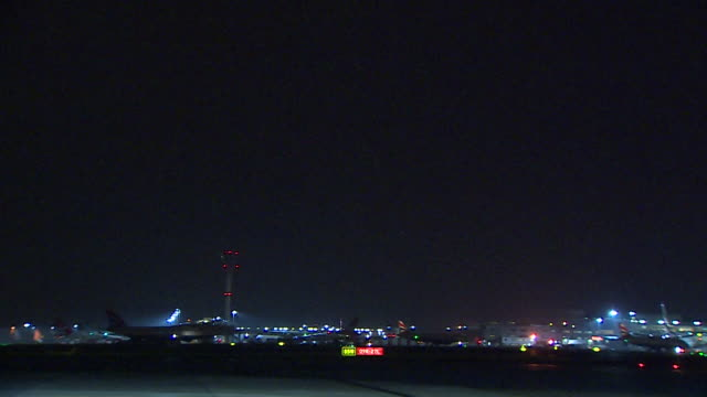 wide shot of a british airways aircraft taking off at night at heathrow airport london - asphalt stock-videos und b-roll-filmmaterial