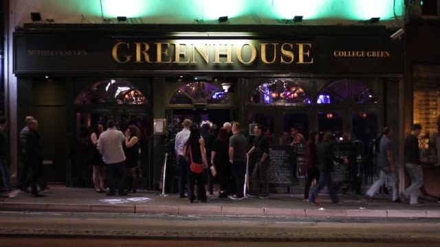 Wide shot of a busy pub exterior with people socializing and drinking alcohol in Bristol city center