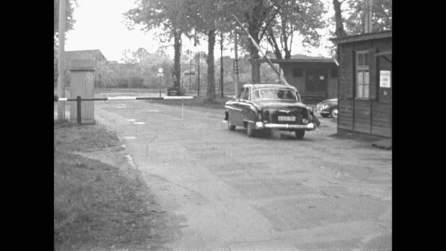 wide shot of a car arriving at a rural border checkpoint between east and west germany and a barrier is lifted allowing it through; 1959. - 1950 1959 stock videos & royalty-free footage