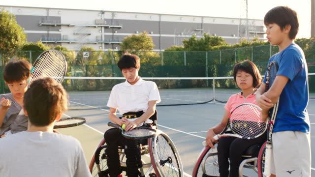 アダプティブテニス選手のチームと話しているコーチのslo moワイドショット - 身体障害点の映像素材/bロール