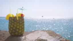 Wide Shot of a Cocktail Served in a Fresh Pineapple at a Beach Resort in 4k