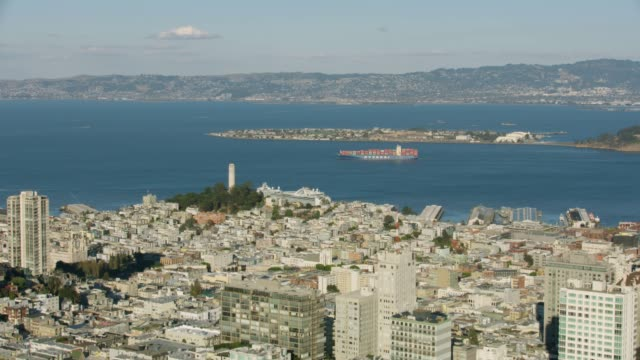 wide shot of a container ship moving along the shore of treasure island with north beach in the foreground - コイトタワー点の映像素材/bロール