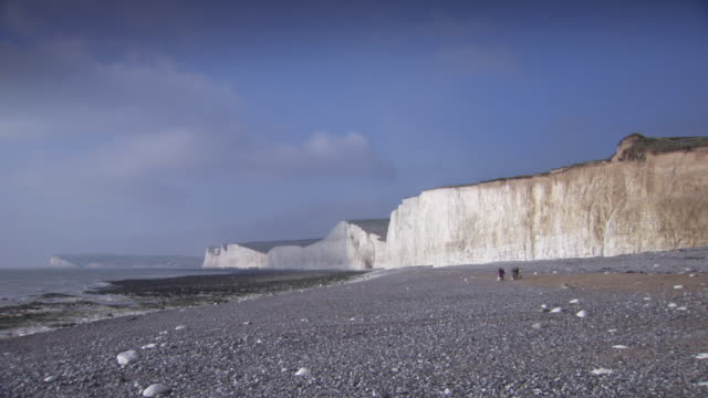 Wide shot of a couple walking their dogs by the Seven Sisters cliffs in East Sussex, UK.