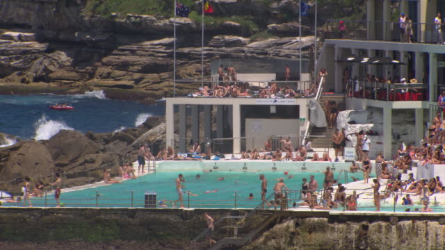 vídeos de stock, filmes e b-roll de wide shot of a crowded bondi icebergs club and pool and bondi to bronte coast walk on a sunny day / tilt from sky down to building / zoomed in shot... - praia de bondi