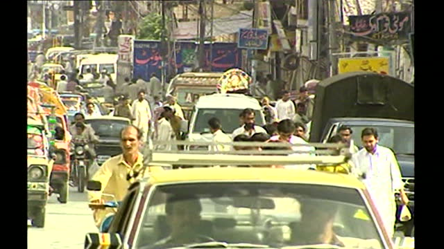 wide shot of a crowded,busy city street with traffic, motorcycles, taxis and people in islamabad, palestine; 14th september, 2001. - bright colour stock videos & royalty-free footage
