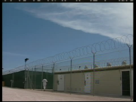 wide shot of a detainee walking by a fence at the camp delta section of guantanamo bay. - war or terrorism or military点の映像素材/bロール