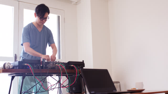 wide shot of a dj practicing on his decks at home - hobbies stock videos & royalty-free footage