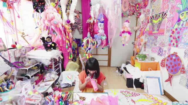 彼女の折衷的なアートスタジオで縫う女性アーティストのワイドショット - 扮装点の映像素材/bロール