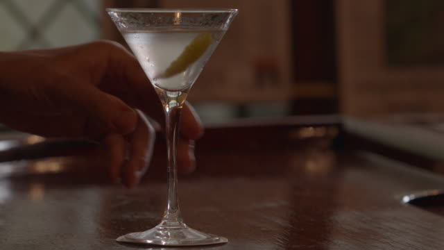 Wide shot of a filled cocktail glass that is picked up and put down