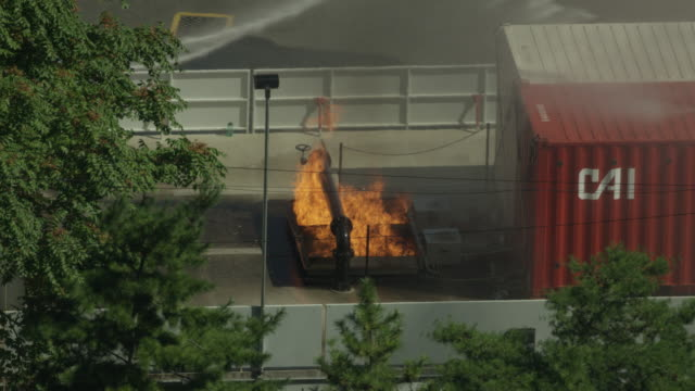 wide shot of a fire in a simulated container ship fire at the fire department of the city of new york training center - fire department of the city of new york stock videos and b-roll footage