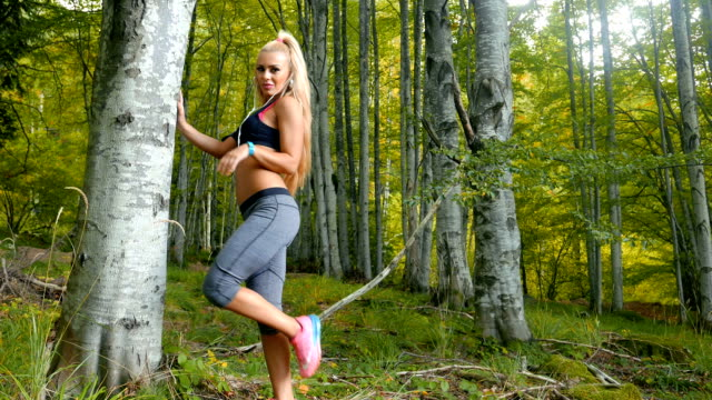 Wide shot of a fitness woman standing outdoors and looking at camera