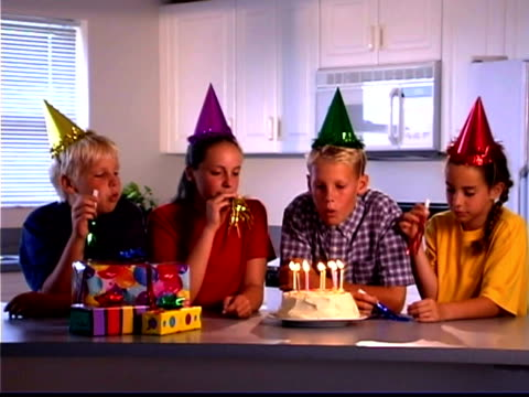 wide shot of a group of friends celebrating a boy's birthday; he blows out the candles on his cake as his friend blow in noisemakers. - bald head island stock videos & royalty-free footage
