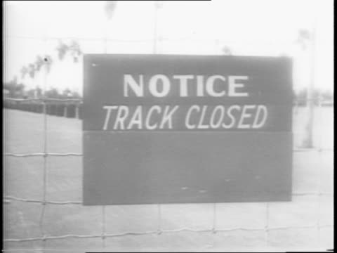 Wide shot of a horse racing track and stands / Shot of a man putting a closed sign on a fence gate / Close up shot of sign that says notice track...