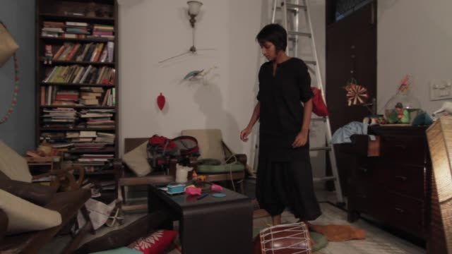 Wide shot of a lady searching something in a messed up living room