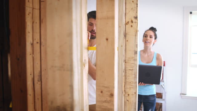 Wide shot of a man and woman discussing their renovation project