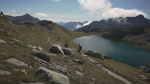 wide shot of a man and woman hiking above a lake in the mountains - switzerland stock videos & royalty-free footage