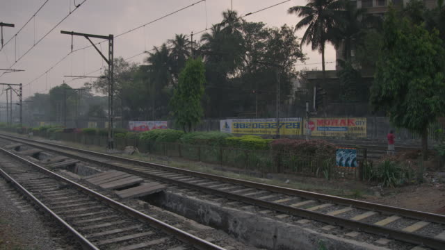 Wide shot of a man combing his hair whilst waiting for a train at dusk Mumbai Maharashtra India FKAD675A Clip taken from programme rushes ABQA810K